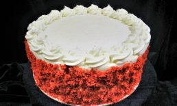 3 layers of traditional Southern red velvet cake with vanilla bean cream cheese buttercream between each layer and blanketing the cake. garnished with bits of red velvet cake crumble